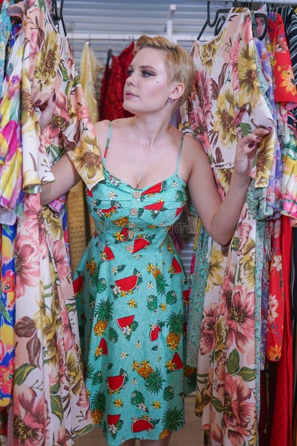 Het mooie weelderige meisje in een modieuze kleding die in de opslag lopen en kiest nieuwe kleren, binnen bekijkend in kostuums o royalty-vrije stock fotografie