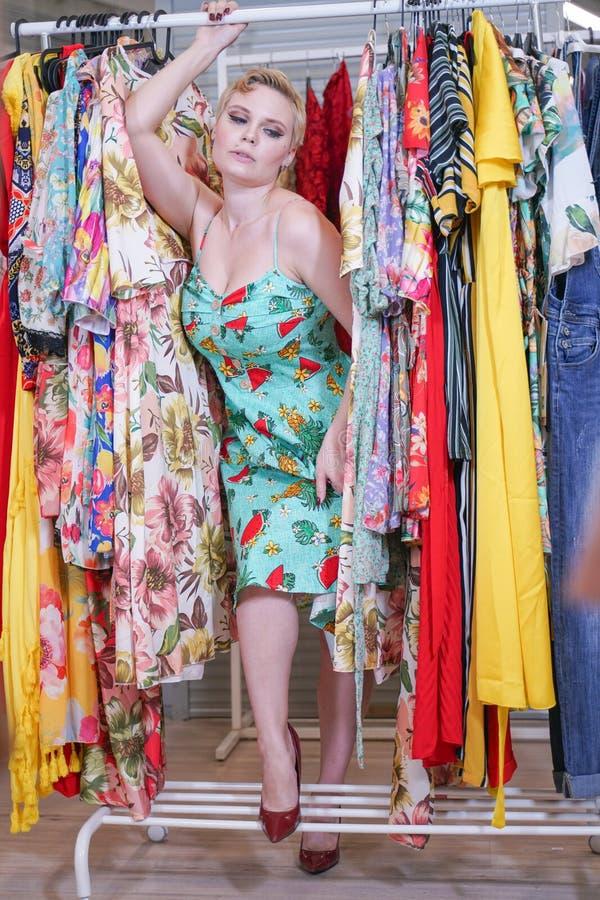 Het mooie weelderige meisje in een modieuze kleding die in de opslag lopen en kiest nieuwe kleren, binnen bekijkend in kostuums o royalty-vrije stock afbeeldingen