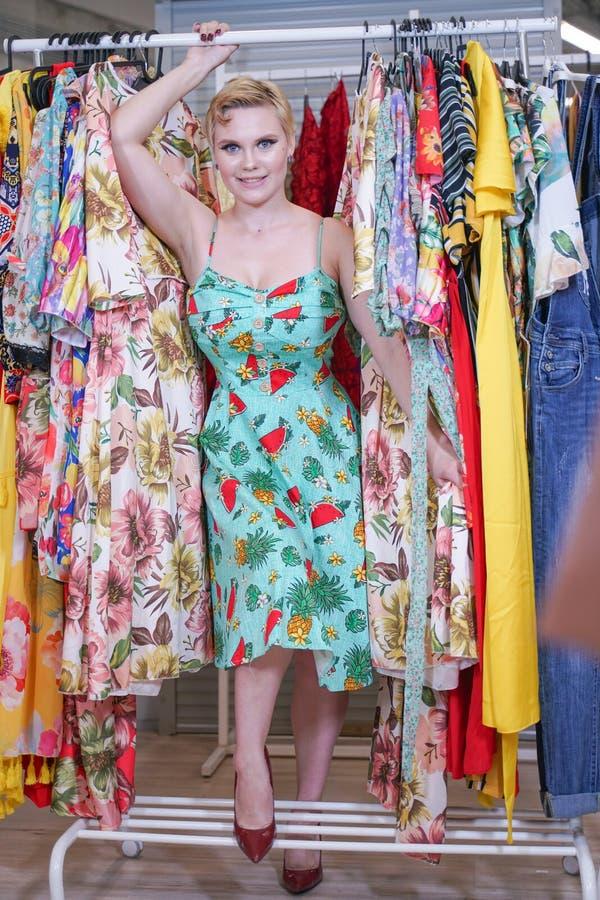 Het mooie weelderige meisje in een modieuze kleding die in de opslag lopen en kiest nieuwe kleren, binnen bekijkend in kostuums o royalty-vrije stock foto