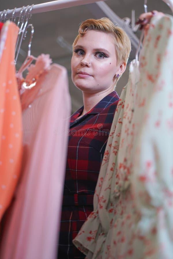 Het mooie weelderige meisje in een modieuze kleding die in de opslag lopen en kiest nieuwe kleren, binnen bekijkend in kostuums o royalty-vrije stock foto's
