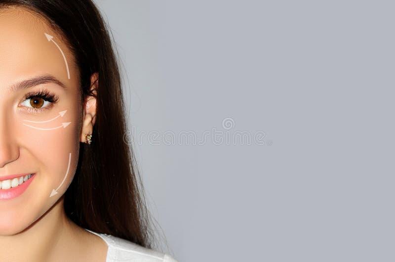 Het mooie wijfje van het close-upportret op grijze achtergrond, geïsoleerd gezicht het opheffen concept met de pijlengezondheid,  royalty-vrije stock afbeelding