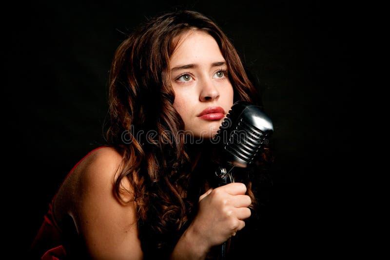 Het mooie zanger zingen met microfoon stock foto's