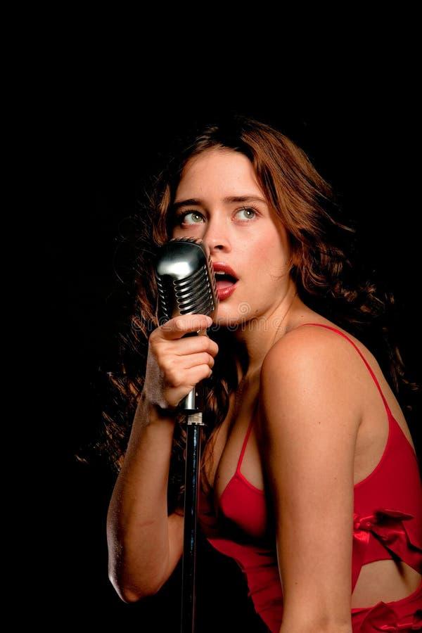 Het mooie zanger zingen met microfoon stock afbeelding