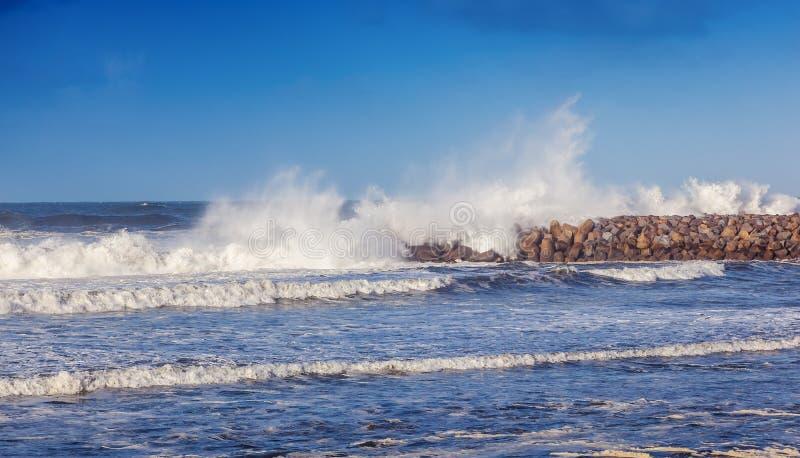 Het mooie zeegezicht, golven breekt over de golfbreker, sto stock afbeeldingen