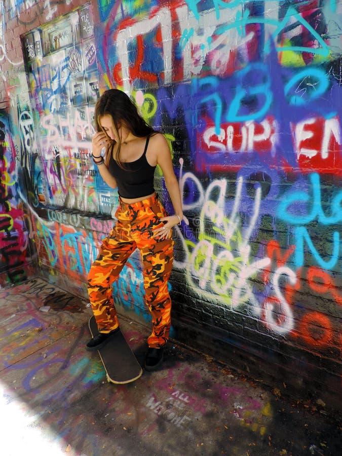 Het mooie zekere donkerbruine meisje van de tienerschaatser royalty-vrije stock foto