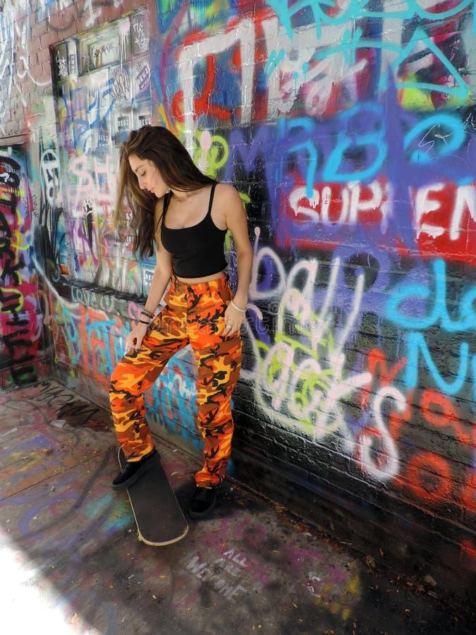 Het mooie zekere donkerbruine meisje van de tienerschaatser royalty-vrije stock afbeeldingen