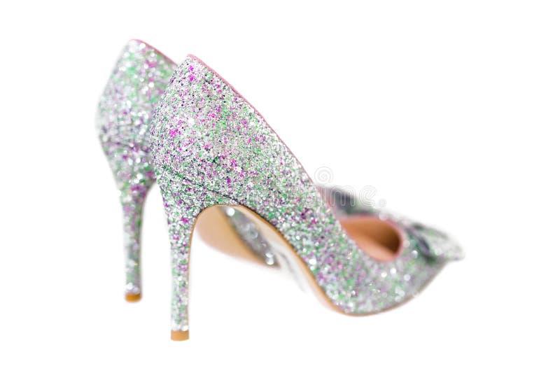 Het mooie zilver schittert hoge hiel vrouwelijke die schoenen op wit worden geïsoleerd Bruid in witte kleding Cinderellaschoenen  stock afbeeldingen