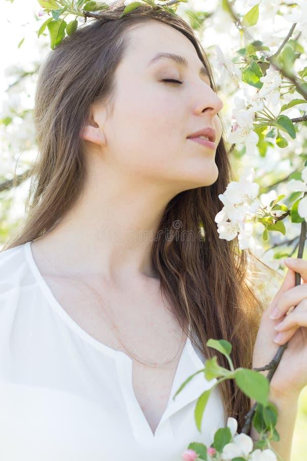 Het mooie zoete meisje in een wit overhemd met bloeiende appelbomen in de tuin loopt heldere warme de zomerdag stock afbeeldingen