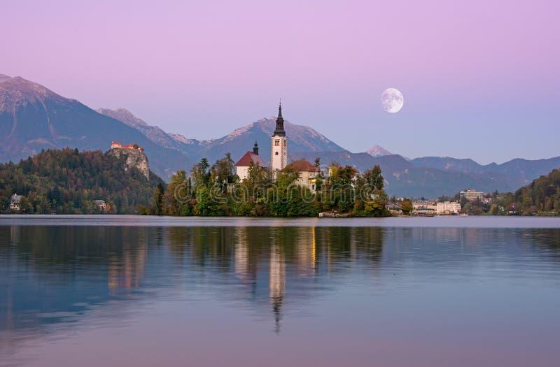 Het mooie zonsopganglandschap van beroemd meer tapte in Slovenië met kleine kerk op groen eiland op purpere hemel met maan af en royalty-vrije stock afbeeldingen
