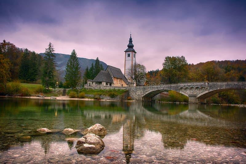 Het mooie zonsopganglandschap van meer Bohinj, het Nationale Park van Triglav, Julian Alps in Slovenië met kerk en de boog overbr royalty-vrije stock afbeelding