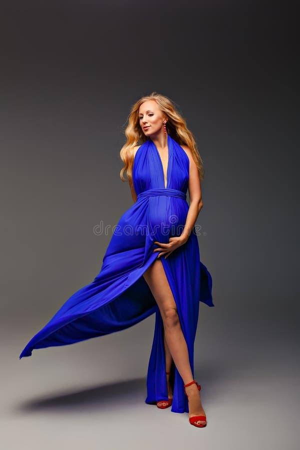 Het mooie zwangere meisjesblonde in een blauwe kleding van zijde bevindt zich in de studio Mooi beeld over zwangerschap royalty-vrije stock foto