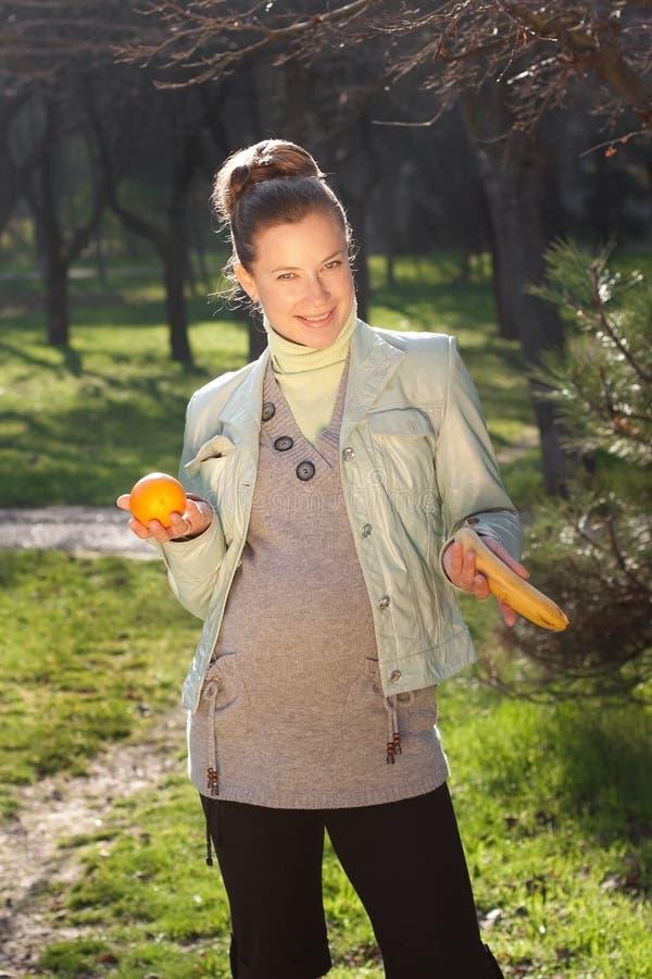 Het mooie zwangere vrouw ontspannen in het park stock afbeelding