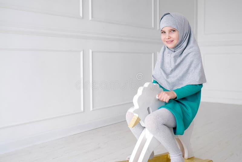 Het moslimtienermeisje in hijab en kleding speelt het berijden op stuk speelgoed paardschommelstoel in haar ruimte stock afbeelding