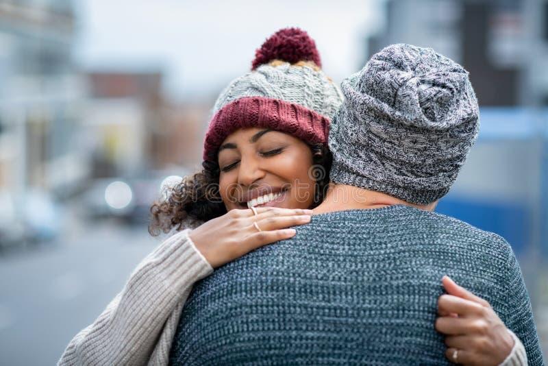 Het multi-etnische paar koesteren openlucht in de winter stock fotografie