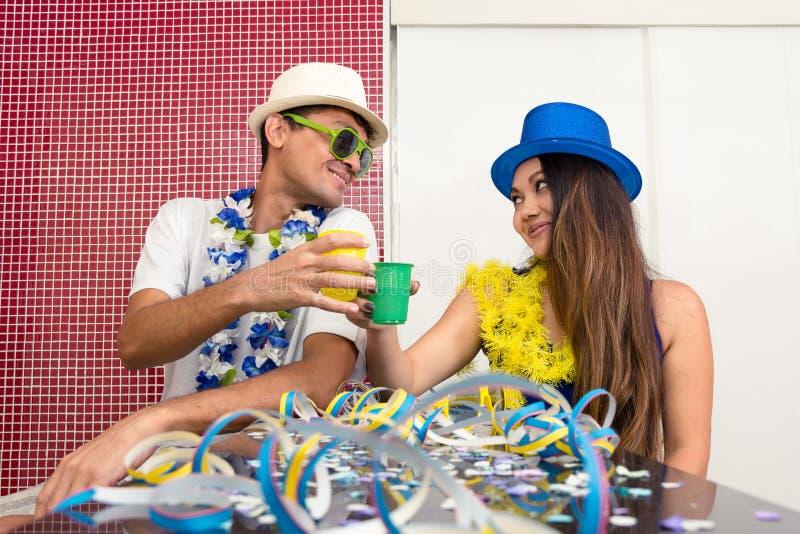 Het multi etnische paar viert Braziliaanse Carnaval gelukkig royalty-vrije stock afbeeldingen