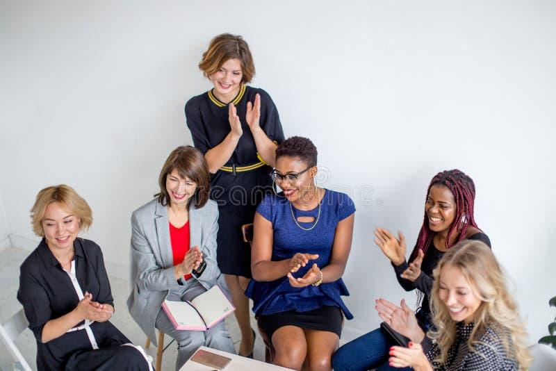 Het multi-etnische vrouwelijke team toejuichen tijdens bedrijfsseminarie in conferentiezaal royalty-vrije stock afbeeldingen