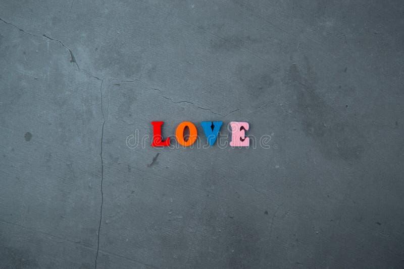 Het multicolored liefdewoord wordt gemaakt van houten brieven op een grijze gepleisterde muurachtergrond stock afbeelding
