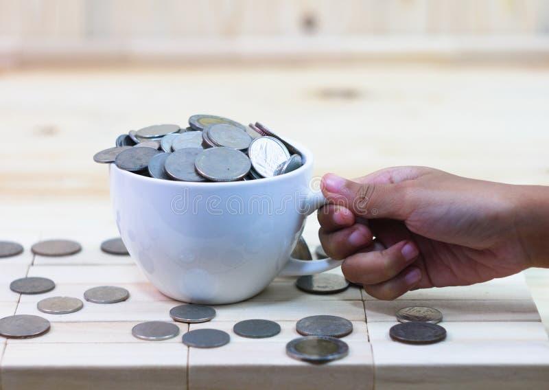 Het muntstuk in een witte koffiekop rust op een houten lijst en aroun stock fotografie