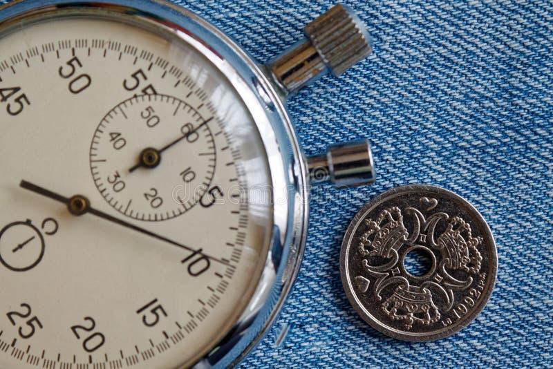 Het muntstuk van Denemarken met een benaming van één kroon (kroon) (achterkant) en chronometer op versleten jeansachtergrond - be royalty-vrije stock afbeeldingen