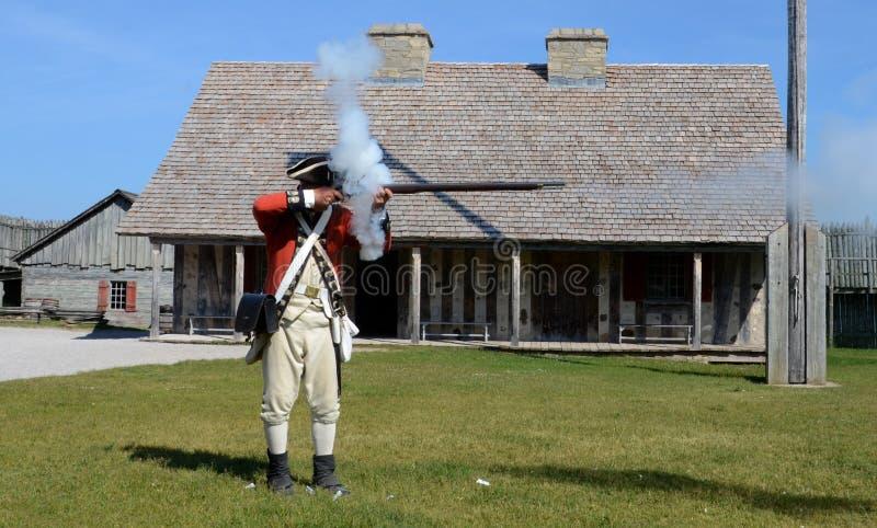 Het musket van re-Enactorbranden bij Fort Michilimackinac royalty-vrije stock fotografie