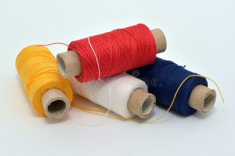 Het naaien kleurde draden: geel, rood, donkerblauw, wit stock afbeelding