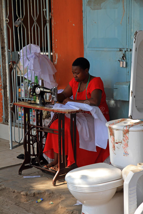 Het Naaien van de vrouw op de Straat naast een Toilet royalty-vrije stock afbeeldingen