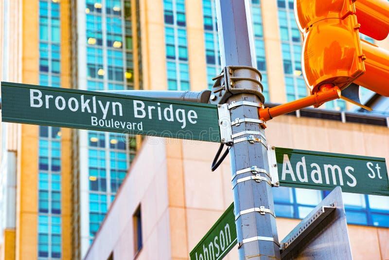 Het naambord van het straatteken van de Brug van Brooklyn en Adams Straat en stock fotografie