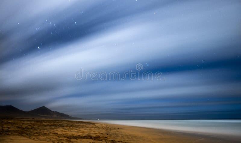 Het nachtbeeld met lange blootstelling en de nacht spelen in beweging mee - strand en bergen mooi wild landschap voor reisavontur stock fotografie