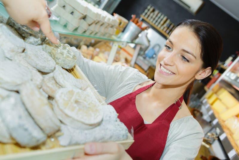 Het nadenkende glimlachen en positieve arbeider bij bakkerij stock fotografie