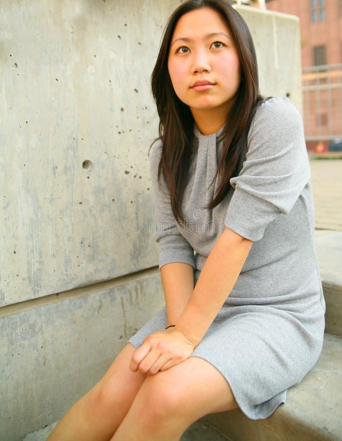 Het nadenkende Jonge Aziatische Meisje zit Openlucht royalty-vrije stock foto