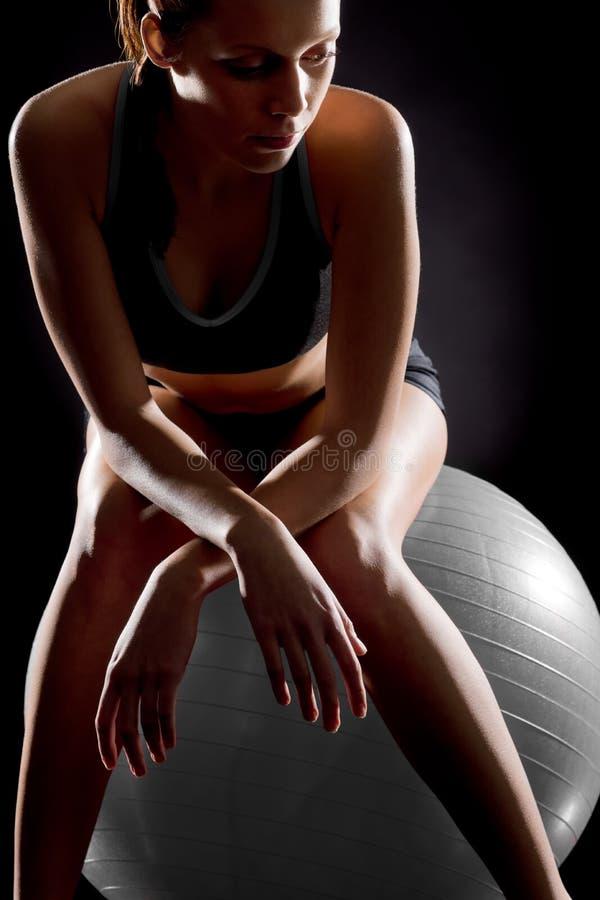 Het nadenkende jonge vrouw ontspannen op geschiktheidsbal stock fotografie