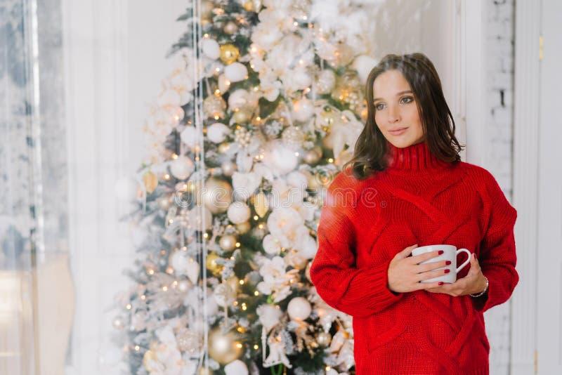 Het nadenkende prettige vrouwelijk kijken in gebreide rode sweater, houdt mok met thee of de koffie, bevindt zich dichtbij Kerstb royalty-vrije stock afbeeldingen