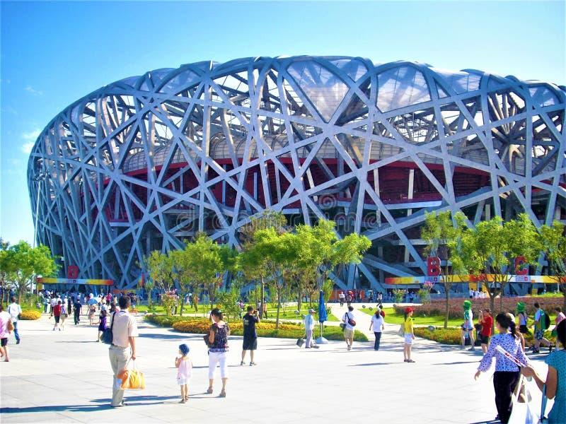 Het Nationale Stadion van Peking, lopende mensen en zonnige dag in China stock afbeeldingen