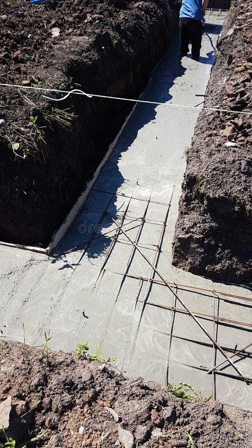 Het natte beton wordt gegoten bij de het staalversterking van het draadnetwerk stock foto