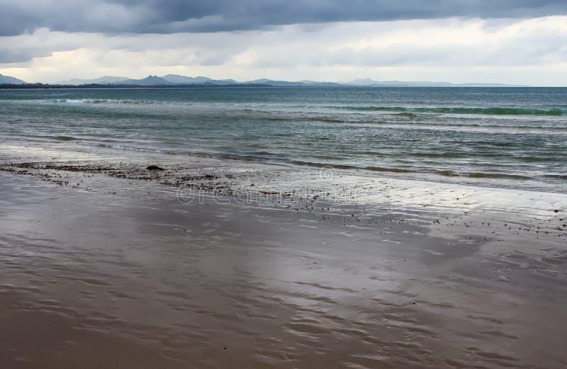 Het natte strand als getijde gaat met blauwe bergenwaaiers achteruit in de afstand onder een stormachtige hemel - Byron Bay NSW A stock foto