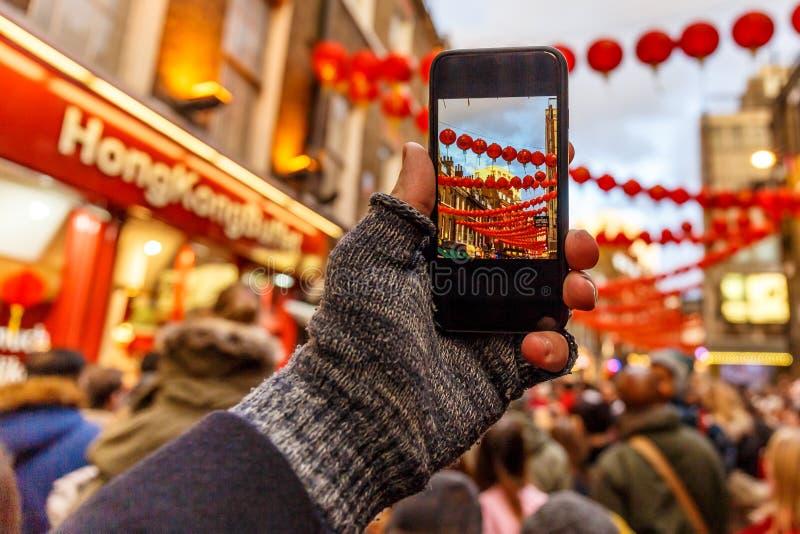 Het nemen en het posten foto van Chinees nieuw jaar met smartphone stock foto's