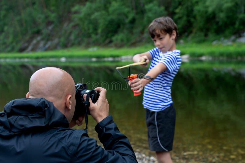 Het nemen van een beeld of een fotospruit in openlucht de mannelijke fotograaf fotografeert een 9 éénjarigenjongen royalty-vrije stock foto