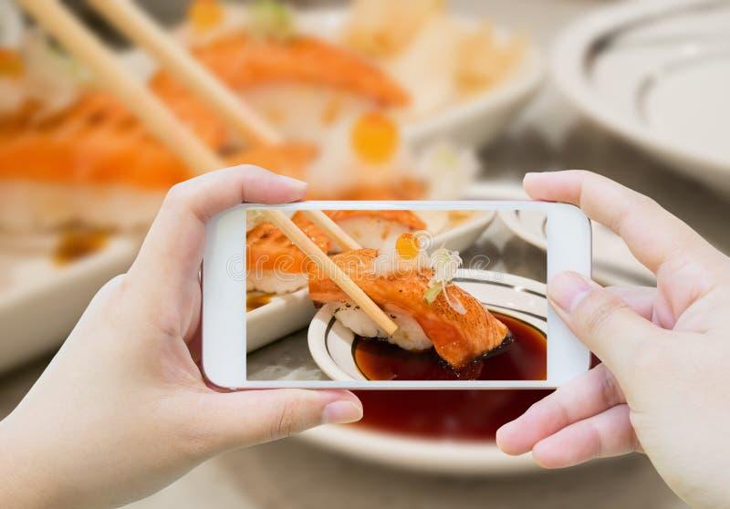Het nemen van foto van Geroosterde zalmsushi in eetstokjes stock afbeelding