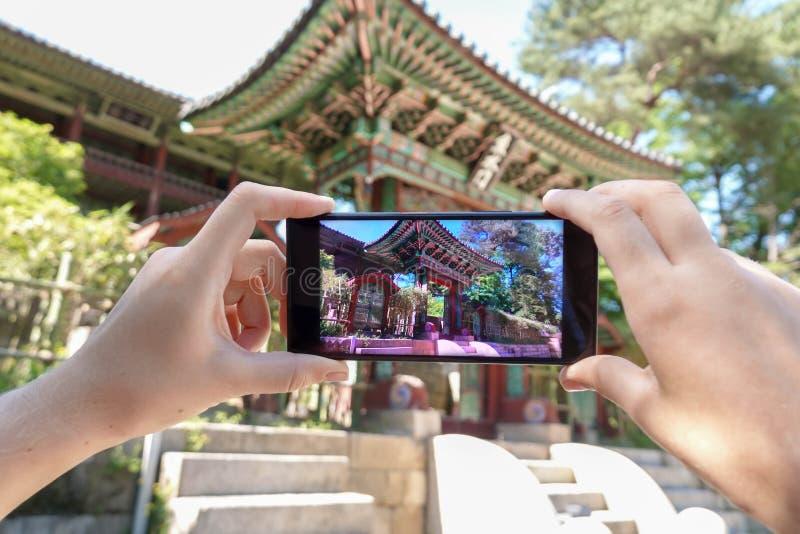 Het nemen van Foto van Koreaanse Architectuur met Mobiele Telefoon Toerisme en Digitale Technologieën stock afbeeldingen
