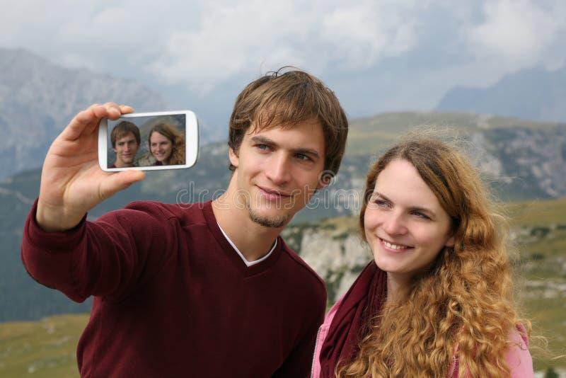 Het nemen van foto's met een smartphone tijdens vakantie in de bergen stock afbeeldingen