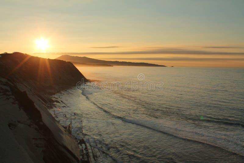 het nemen van foto's van prachtige zonsondergang op Atlantische kust op de richel in horizontale mening stock afbeelding