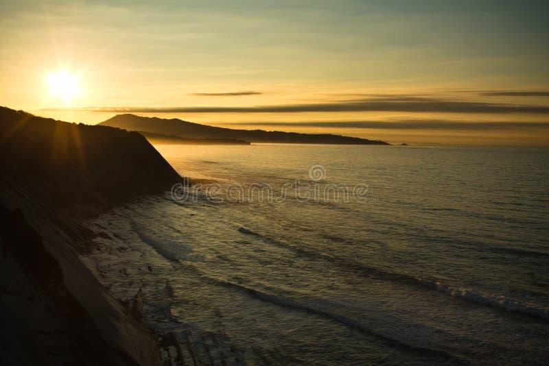het nemen van foto's van prachtige zonsondergang op Atlantische kust op de richel in horizontale mening royalty-vrije stock foto's