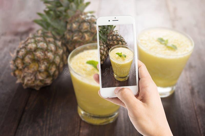 Het nemen van foto van ananas smoothie op houten lijst stock foto