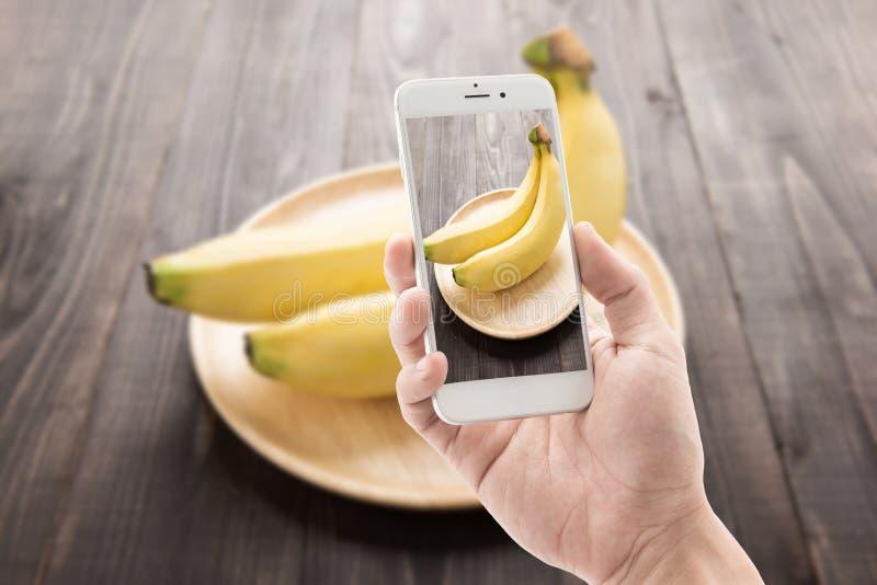 Het nemen van foto van bananen op houten achtergrond royalty-vrije stock foto