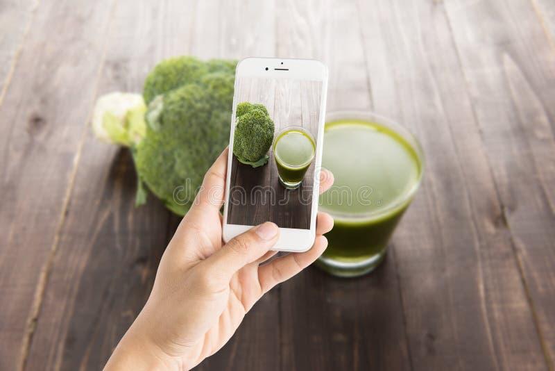 Het nemen van foto van broccolisap op houten lijst royalty-vrije stock afbeelding