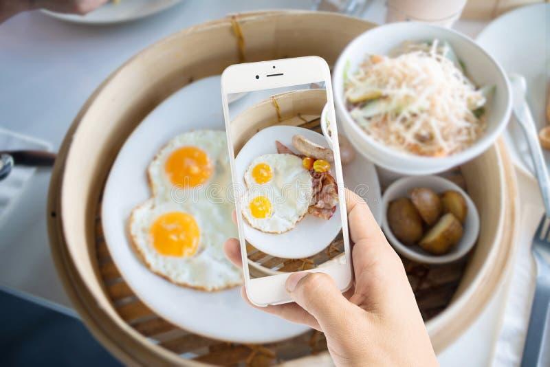 Het nemen van foto van ei met worsten voor ontbijt royalty-vrije stock afbeelding
