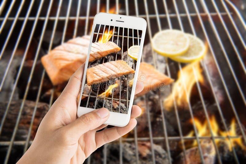Het nemen van foto van geroosterde zalm met citroen op de vlammende grill stock afbeeldingen