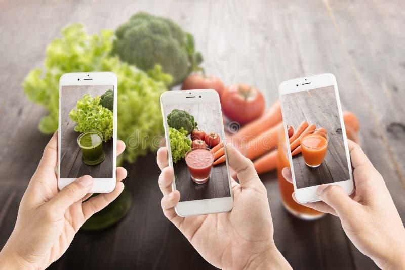 Het nemen van foto van Groentesappen met verse ingrediënten stock afbeelding