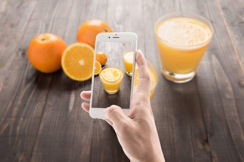 Het nemen van foto van jus d'orange en sinaasappel op de houten achtergrond royalty-vrije stock foto