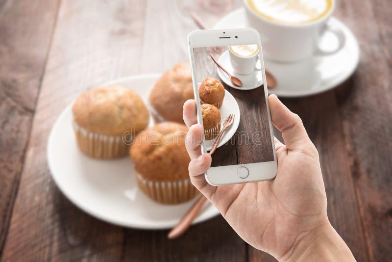 Het nemen van foto van muffin en koffie op houten lijst royalty-vrije stock foto's